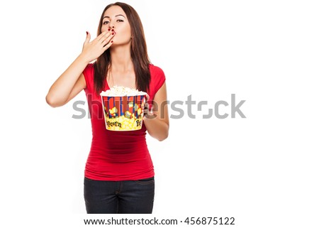 woman in glasses holding popcorn in hand and sends an air kiss - stock photo