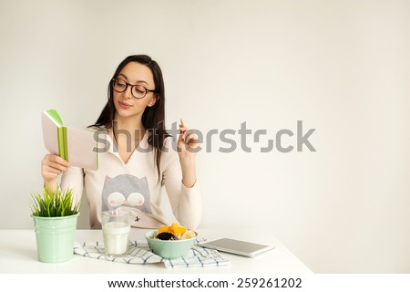 Woman in glasses making notes in notepad with porridge, milk and tablet on table, copy space - stock photo