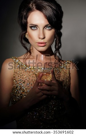 Woman in gold dress holding glass of wine. - stock photo