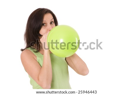 woman  in green dress is blowing green balloon - stock photo
