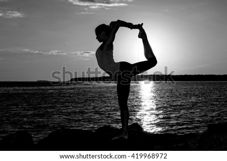 Woman in green shirt and black leggings making youga exercises on the stones with sea and city background in sunset time. Natarajasana pose in yoga. King dancer yoga pose. Black and white picture. - stock photo