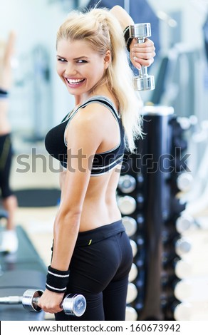 Woman in gym exercising with dumbbells  - stock photo