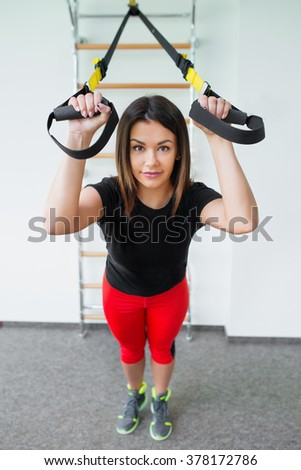 Woman in gym using equipment trx. Attractive woman does crossfit push ups with trx fitness straps in the gym - stock photo