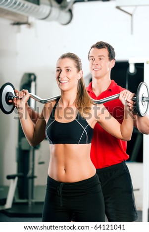 Woman in gym with personal fitness trainer exercising power gymnastics with a barbell - stock photo