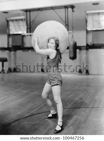 Woman in gymnasium with huge ball - stock photo