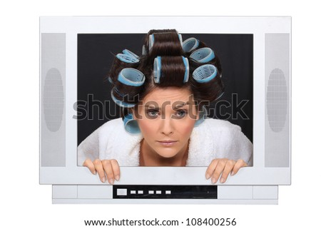 Woman in hair rollers trapped in television - stock photo