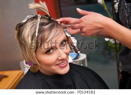 woman in hairdresser salon on preparation for hair coloring - stock photo