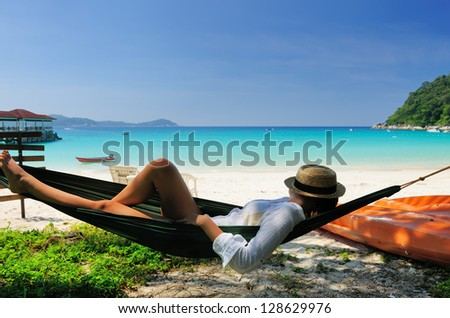Woman in hammock on tropical beach at Perhentian islands, Malaysia - stock photo