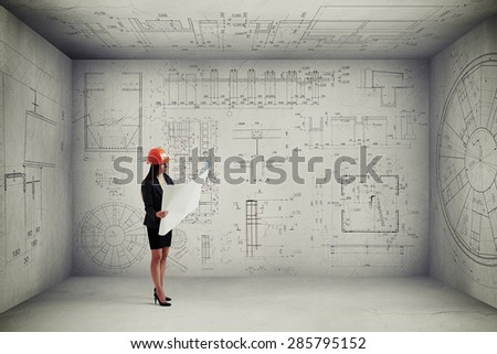 woman in hardhat with blueprint standing in empty room with prints on the walls and ceiling  - stock photo
