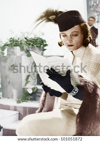 Woman in hat and veil reading sheet music - stock photo