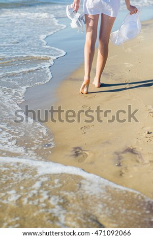 Woman in hat and white dress walking on the beach. Back view. Cropped image on the legs.