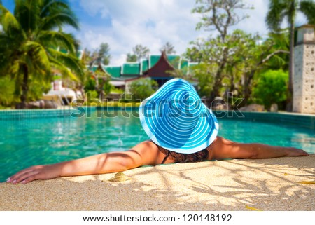 Woman in hat at relaxation on tropical holidays - stock photo