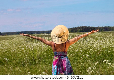 woman in hat enjoying nature in a green field - stock photo