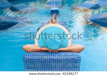 Woman in hat relaxing on swimming pool bed - stock photo