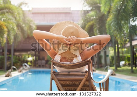woman in hat taking sunbath near swimming pool - stock photo