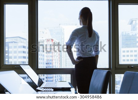 Woman in he office looking out the window.  - stock photo
