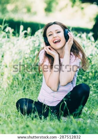 Woman in headphones. Emotional young woman in headphones  - stock photo