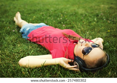 Woman in headphones lying on the grass. Young smiling woman listening to music while relaxing on a green lawn in spring or summer. Freedom and happiness concept.  - stock photo