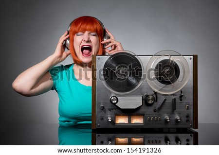 Woman in headphones with a retro reel audio tape recorder on dark background - stock photo