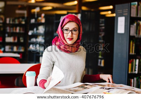 Woman in headscarf sitting at the desk with books studying at the library - stock photo