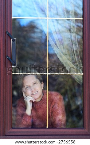 Woman in her fifties looking through the window. - stock photo