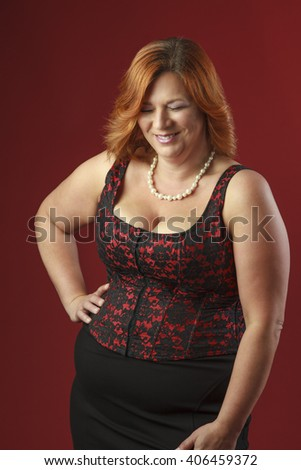 woman in her forty wearing a red corset, laughing - stock photo