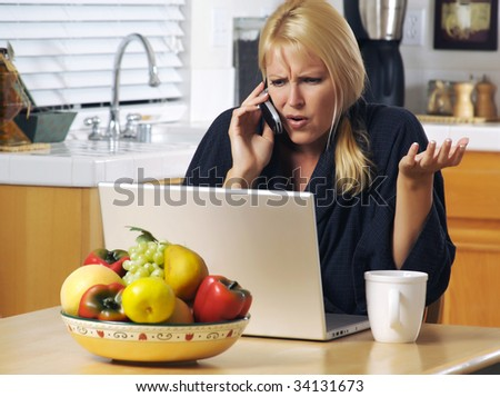 Woman in her kitchen on cell phone sitting in front of laptop. Computer problems? - stock photo