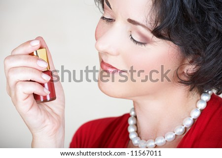 woman in her nid 30s or early 40s holding nail polish bottle in her hand and smiling - stock photo