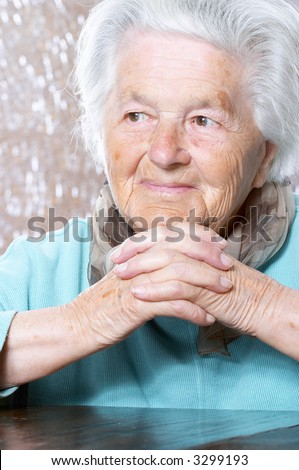 Woman in her nineties with her hands clasped under the chin - stock photo