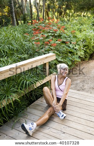 Woman in her 50s in workout clothes and running shoes doing stretching exercises wooden park bridge