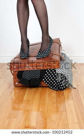 Woman in high heel shoes standing on leather suitcase overfilled with fashion clothing. - stock photo