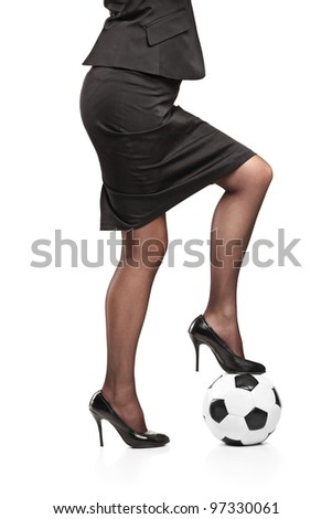 Woman in high heeled shoes standing on a soccer ball isolated on white background - stock photo