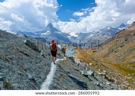 woman in hiking in high mountains. snow-capped peaks, glaciers and Fantastic sky background with blue clouds
