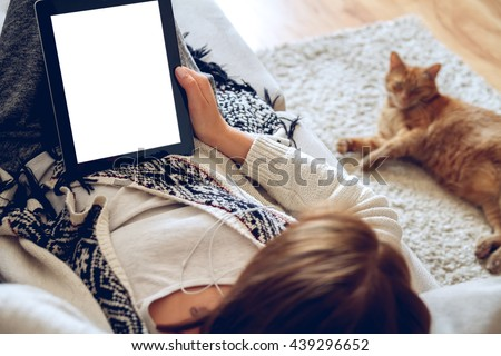 Woman in home cozy clothes lying on a sofa using tablet with headphones, looking at a lazy red cat sprawled on the carpet beside. Online education concept. e-learning. back view. Pet shop concept - stock photo