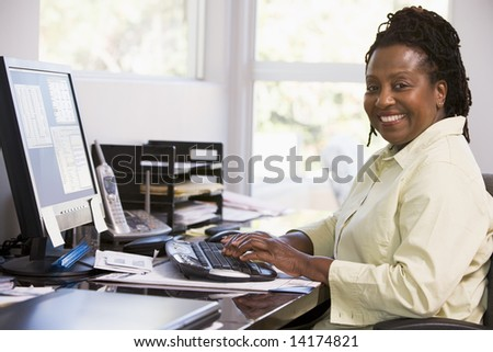 Woman in home office using computer and smiling - stock photo