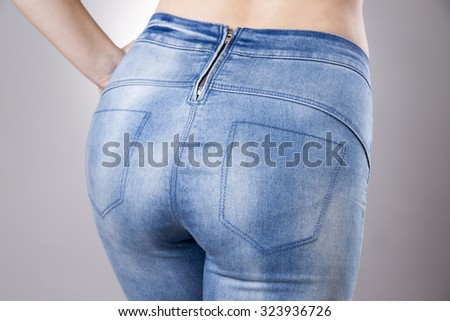 Woman in jeans close up. Beautiful female hips and buttocks on a gray background - stock photo