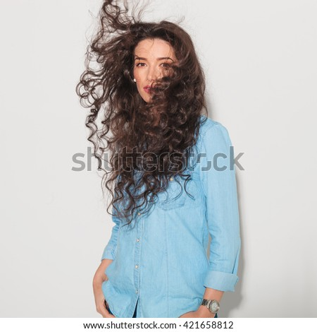 woman in jeans clothes having her hair blown by the wind in studio - stock photo
