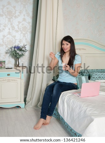 woman in jeans eat yogurt in bed with a laptop