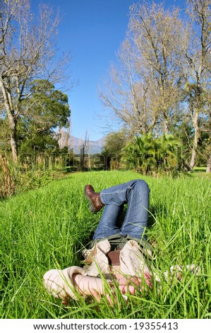 Woman in jeans lies in park on grass. Shot in Vergelegen estate, near Cape Town, Western Cape, South Africa. - stock photo