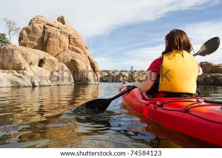 Woman in Kayak Paddling in Lake - stock photo