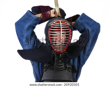 Woman in kendo (japanese fencing) helmet determined to attack. - stock photo