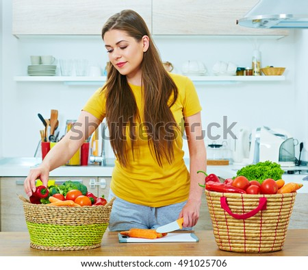 woman in kitchen cooking vegetables. young woman with long hair casual clothes wearing