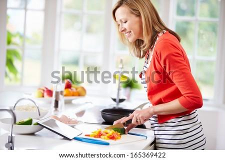 Woman In Kitchen Following Recipe On Digital Tablet - stock photo
