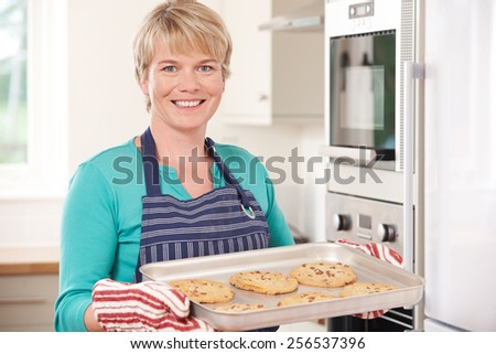 Woman In Kitchen Holding Tray With Home Baked Cookies - stock photo