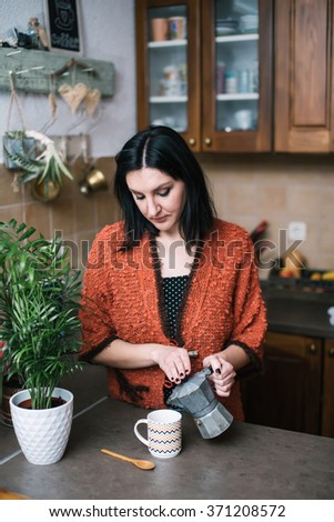 Woman in kitchen pouring coffee from vintage coffee maker - stock photo