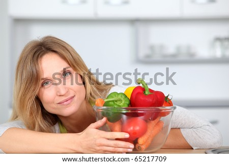 Woman in kitchen ready to prepare meal with vegetables - stock photo