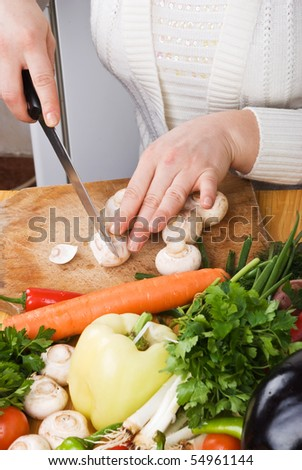 Woman in kitchen slicing  mushroom on wood board and variety of fresh vegetables
