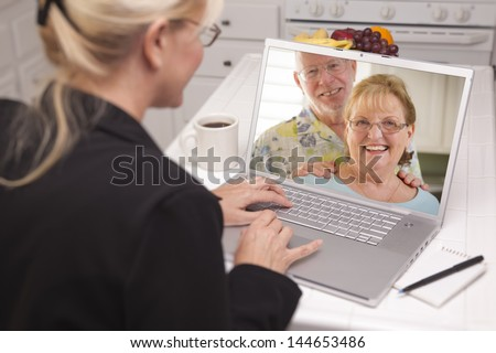 Woman In Kitchen Using Laptop - Online Chat with Senior Couple or Parents On Screen. - stock photo
