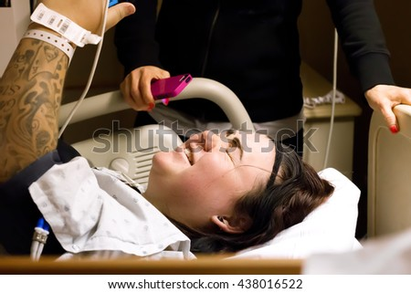 Woman in labor talking on the phone while having a contraction as her step mother stands in the background with a phone of her own.