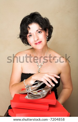 Woman in lace black dress with short curly hair, wearing pearls, holding shoes on top of red gift boxes